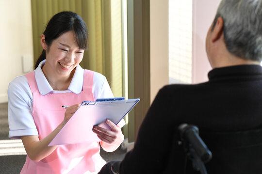 カウンセリング(問診)をする介護士とシニアの男性