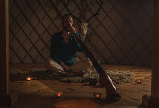 Man playng on didgeridoo by candlelight and tibetian bowl.