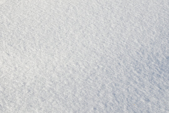 White snow texture on clear day. Winter background. Snow drifts. white snowflakes background, rough pattern of snow texture