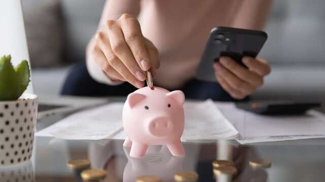 Close up young woman putting coin in piggybank, calculating domestic expenditures, managing household bills, planning monthly payments using mobile e-banking, people and money savings economy concept.