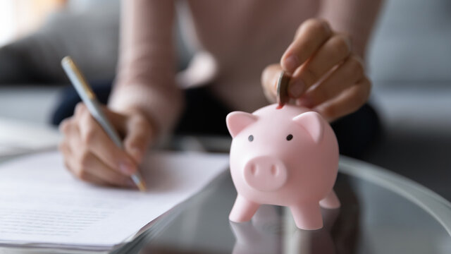 Close up young woman putting coin in piggy bank, writing household expenses on paper, planning domestic monthly bills payments or medical insurance services, managing savings or calculating taxes.