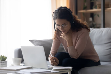 Focused millennial woman in eyeglasses wearing headset with microphone, involved in studying on...