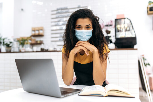 Young African American female small business owner or waitress, wearing medical mask and black apron, studying small business monthly financial statement using laptop, looks at the camera, sitting in