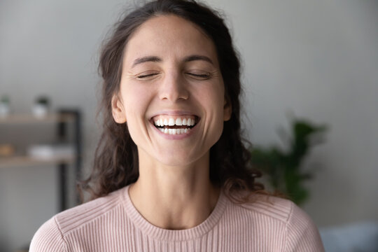 Close up head shot overjoyed young beautiful woman laughing with closed eyes. showing sincere smile with perfect white teeth. Happy millennial lady having fun, communicating distantly with friends.