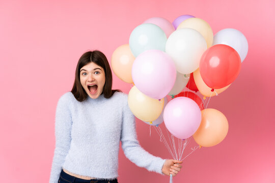 Young Ukrainian teenager girl holding lots of balloons over isolated pink background with surprise facial expression