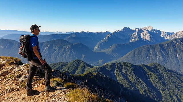 A man in a hiking outfit with a panoramic view on the haze shrouded valley from the way to Mittagskogel in Austrian Alps. Clear and sunny day. Endless mountain chains. Outdoor activity. Achievement