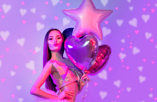 Valentine Beauty girl with colorful air balloons laughing, on violet background. Beautiful Happy Young woman. holiday party. Joyful model having fun, playing and celebrating with red heart balloons