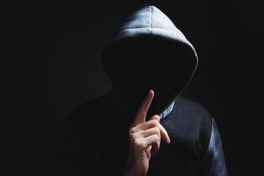 hooded man making silence gesture