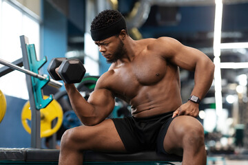 Concentrated african american muscular guy exercising with barbell