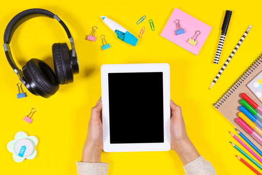 Kid hands holding e-book. Headphones and school supplies on yellow background. Online learning, back to school, remote education at home. Top view