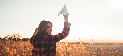 Obraz Travelling woman with paper airplane enjoying life and freedom at the land at sunset. Arms outstretched and happiness - fototapety do salonu