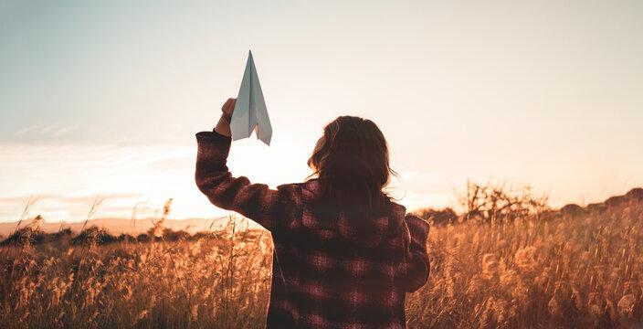 Giovane ragazza tiene in mano un aeroplano di carta. Vista di un campo al tramonto.