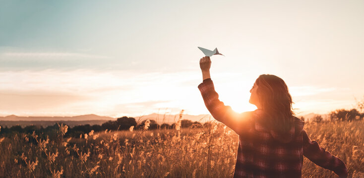 Travelling woman with paper airplane enjoying life and freedom at the land at sunset. Arms outstretched and happiness