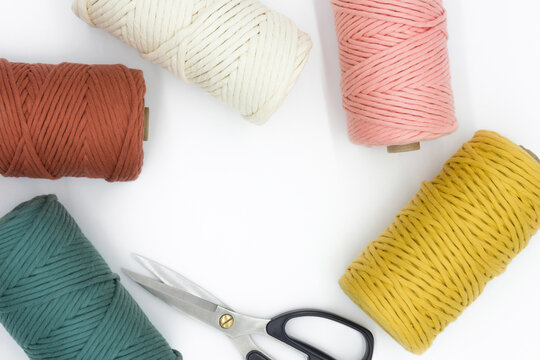 Close-up view of the colorful single strand cotton cords and scissor for macrame DIY handcraft isolated on white background.