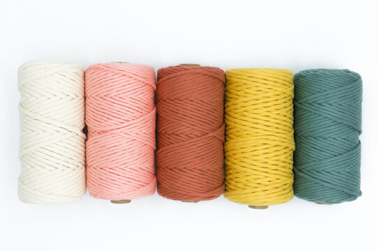 Close-up view of the colorful single strand cotton cords for macrame DIY handcraft on white background.