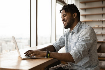 Fototapeta Smiling confident black african male correspond with client friend online typing texting email message on laptop keyboard. Happy young afro man skilled gamer enjoy playing pc video game in good mood obraz
