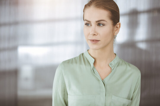 Beautiful adult business woman dressed in green blouse standing straight in sunny office. Business headshot