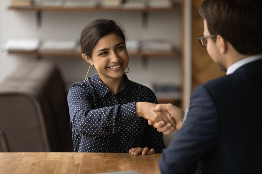 Greetings, you are hired. Happy young indian female successful job seeker shake hand of male hr manager being accepted on vacant place. Diverse business partners handshake close deal come to agreement