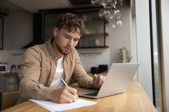 Young guy student prepare research essay at modern kitchen surf internet use laptop write up information to paper report by hand. Focused man freelancer work from home make list of data from pc screen