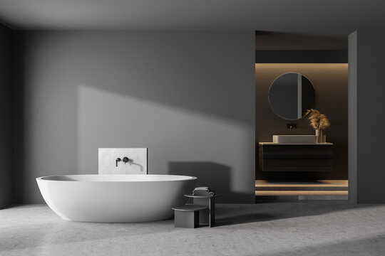 Modern bathroom interior with dark concrete walls, gray floor, white bathtub and sink. 3d rendering