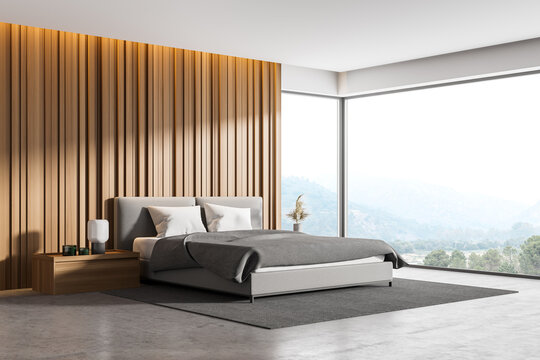 Corner of master bedroom with white, beige and wooden walls, panoramic window with countryside view, comfortable king size bed standing on gray carpet and concrete floor. 3d rendering