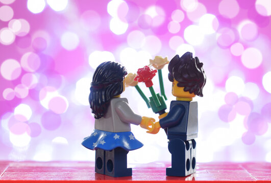 Loerrach, BW  Germany - January, 31th 2021: Lego minifigures couple in love with flowers against a light. Editorial illustrative image of valentines day holiday. Studio shot.
