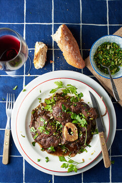 Ossobuco alla Milanese dressed with gremolata on a table of a traditional trattoria. Italian cuisine.