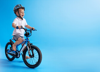 Cute boy learing how to ride a bike