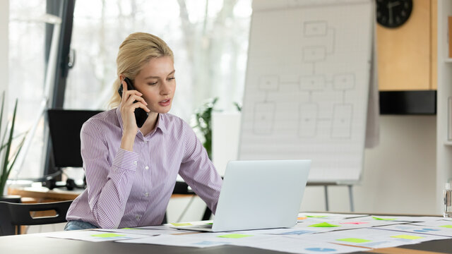 Young female entrepreneur working in office alone. Busy employee using laptop at desk with reports, talking on mobile phone, making or answering call. Sales manager giving consultation to client.