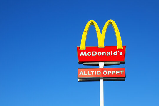 Sodertalje, Sweden - January 31, 2021: The McDonalds sign outside the hamburger restaurant with an additional sign allways open in Swedish against a blue sky.