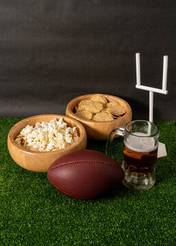 American football party. American football ball, beer, snacks and goal post on green grass and black background