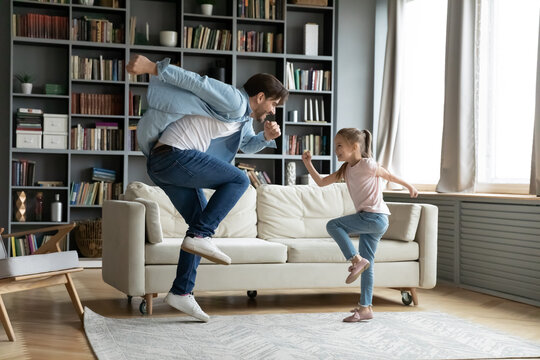 Crazy young happy energetic caucasian father having fun with adorable small 7s kid daughter, dancing to disco pop music together in living room, enjoying domestic active family pastime at home.