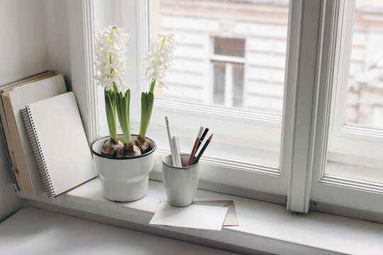 Easter spring still life. Greeting card, books and diary on window sill. White hyacinth in flower pot. Blank greeting card mockup. Pencils in ceramic holder. Home office concept. Scandinavian interior