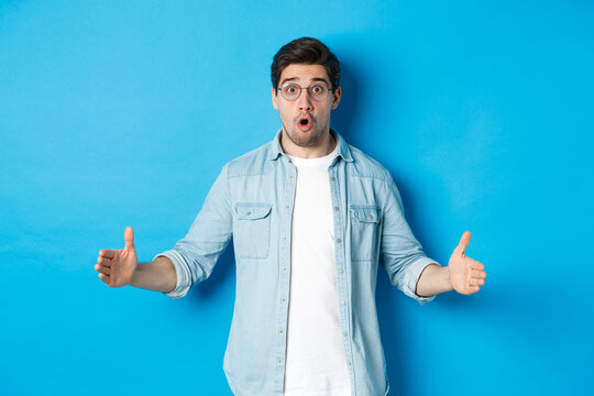 Surprised handsome man holding something big, showing large size with amazed face, standing over blue background