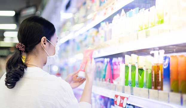 Asian woman wearing surgical mask and hand holding the bottle of facial foam for shopping in the aisle of the skincare department in supermarket