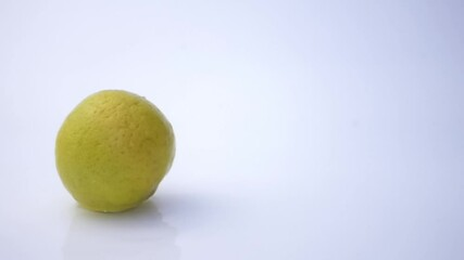 Fototapete - Ripe lemon falls to the wet floor on white background in slow motion. Water splashing at the white floor when ripe lemon is falling on.