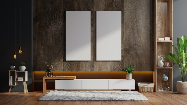 Poster mockup with vertical frames on empty dark wooden wall in living room interior with cabinet.