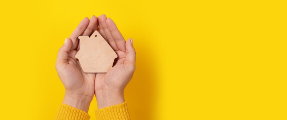 house toy in hands over yellow background, panoramic mock-up - fototapety na wymiar