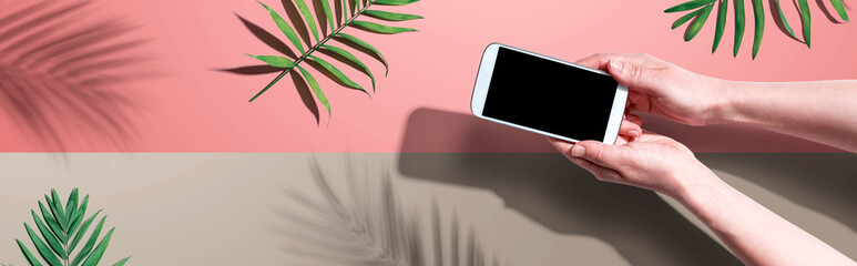 Smartphone with tropical palm leaves and shadow - flat lay Wall mural