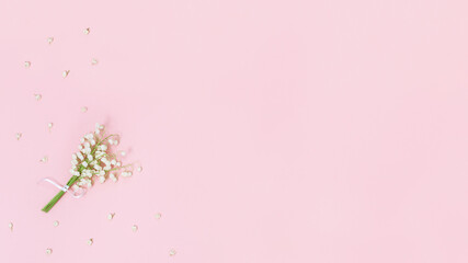 Small bouquet of lilies of the valley on soft pink background with free space for text. Spring banner with natural flowers.