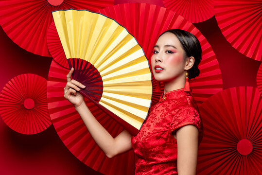 Beautiful gorgeous Asian woman in traditional Chinese dress with colorful make up holding golden fan in oriental style red background
