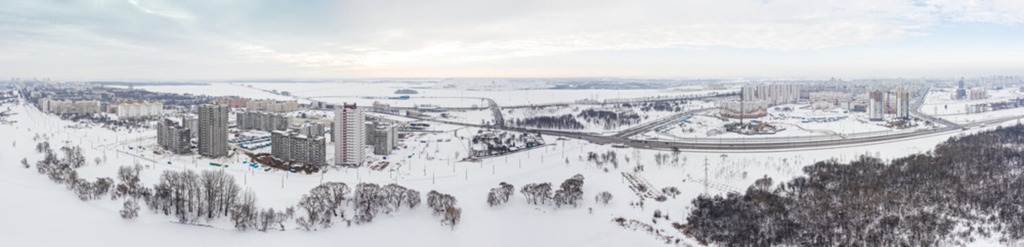 panoramic aerial view of city suburb area with buildings, roads and construction site. winter cityscape on cloudy sky background. Minsk, Belarus