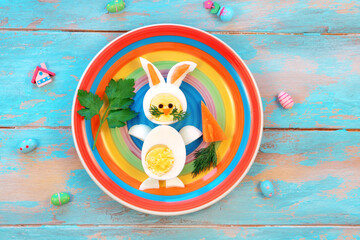 Breakfast idea for kids. Bunny rabbit made of boiled eggs on multicolored plate, blue wooden...
