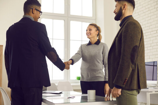 Happy young business people shaking hands to confirm collaboration after making successful deal in negotiation meeting in the office. Smiling company manager or bank adviser thanking client for trust