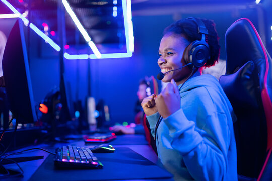 Young American African smile woman professional gamer win in online video game with headphones, neon background