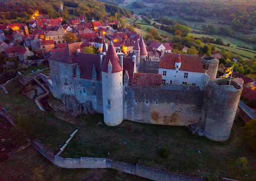 Aerial view of picturesque autumn landscape of Chateauneuf with medieval fortress on stone ledge at dusk, France