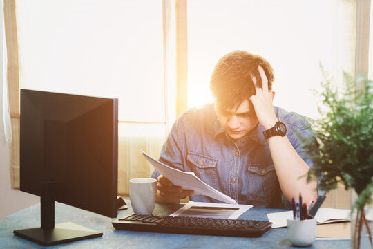 Young Asian men are stressed out in business office. Looking at expense bill and the other hand on head, thinking about finding money to pay credit card debt and all bills. Concept financial problems.