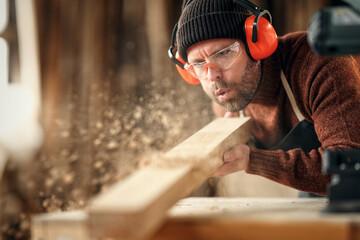 Fototapeta Carpenter blowing sawdust from wooden plank obraz