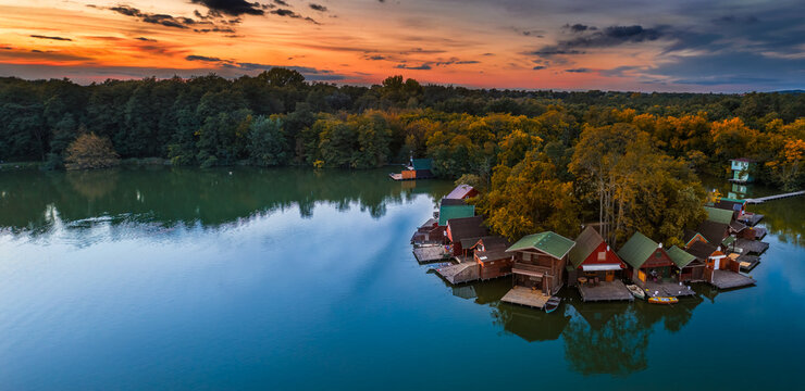 Tata, Hungary - Aerial panoramic view of a beautiful autumn sunset over wooden fishing cottages on a small island at Lake Derito (Derito-to) at Tata in October