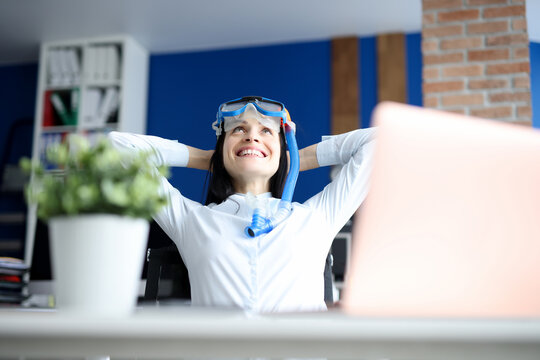 Woman in diving mask dreaming of sea at workplace. Rest during pandemic concept